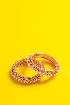 Złota biżuteria na żółtej powierzchni