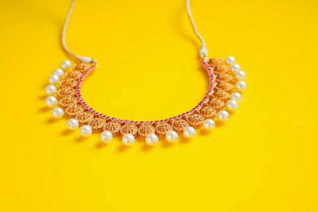 Złota biżuteria na żółtym tle