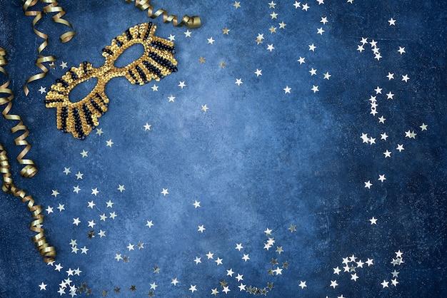 Złota błyszcząca maska i serpentyna ze złotymi gwiazdami na niebieskiej ścianie. widok z góry, miejsce na kopię.