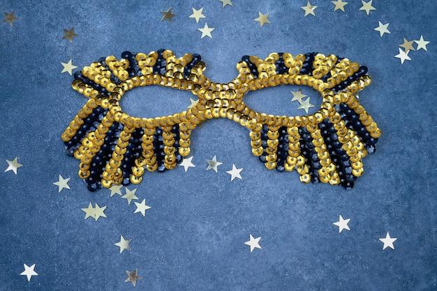 Złota błyszcząca maska ze złotymi gwiazdami na niebieskiej ścianie. widok z góry, miejsce na kopię.