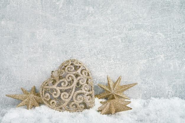 Złota bożenarodzeniowa dekoracja w śniegu na szarym tle. .