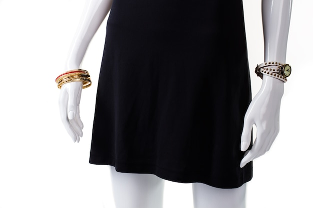 Złota bransoletka i czarna sukienka. żeński manekin nosi nowe bransoletki. miękka sukienka z dodatkami na nadgarstki. popularne modne akcesoria dla pań.