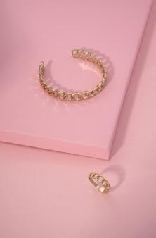Złota bransoletka i pierścionek w kształcie łańcuszka na różowej powierzchni