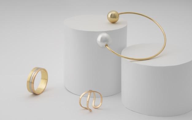 Złota bransoletka z perłą i złote pierścienie na białej okrągłej platformie na białej powierzchni