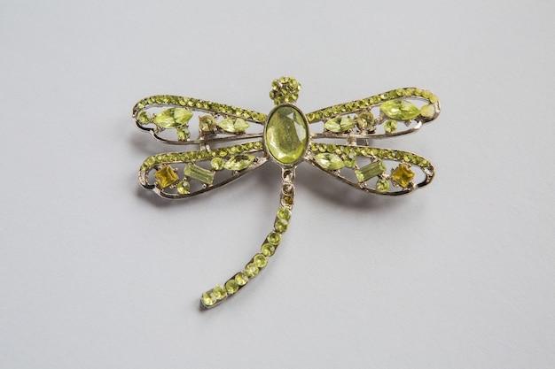 Złota broszka w kształcie z zielonych kamieni na białej powierzchni