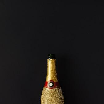 Złota butelka szampana na ciemnej powierzchni