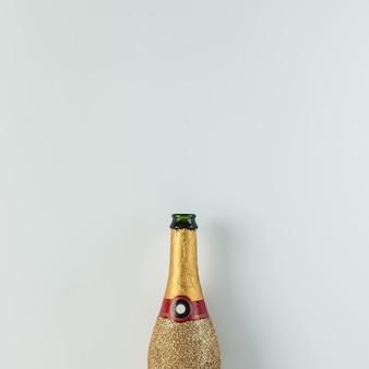 Złota butelka szampana na jasnej powierzchni