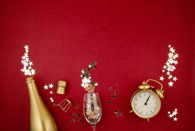 Złota butelka szampana, szkła, budzika i konfetti na czerwonym tle.