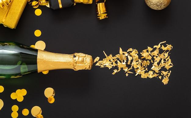 Złota butelka szampana wylewa się ze złotych błysków w ramach złotej świątecznej dekoracji.