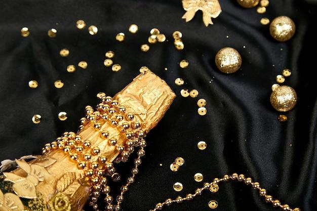 Złota butelka szampana z gwiazdami konfetti i streamerami imprezowymi