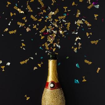 Złota butelka szampana z konfetti na ciemnej powierzchni