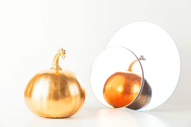 Złota dekoracyjna dynia na jasnym tle z odbiciem w okrągłych lustrach