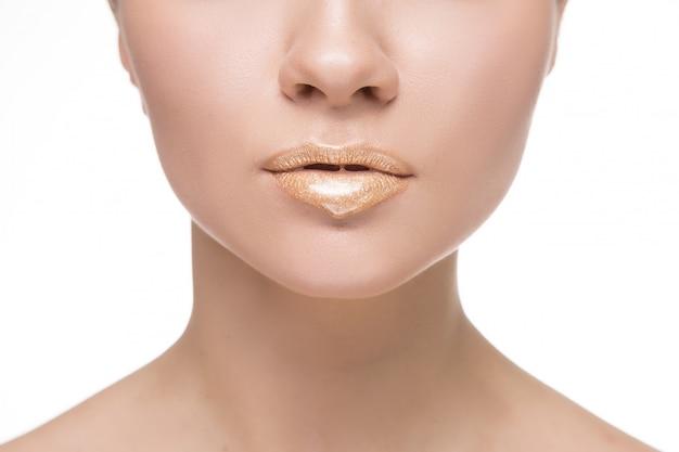 Złota farba kapie z ust, złote płynne krople na ustach pięknej modelki, złota metaliczna farba rozmazuje makijaż. piękno kobiety twarzy makeup zakończenie up.