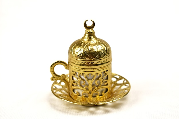 Złota filiżanka kawy na białym tle