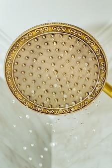 Złota głowica prysznicowa na ścianie z fajansem