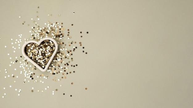 Złota gwiazda błyszczy w kształcie serca na szarym pastelowym modnym tle na walentynki