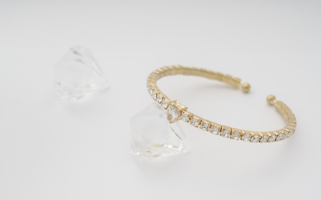 Złota i diamentowa bransoletka w kształcie serca na białej ścianie