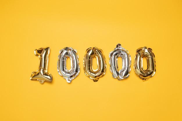 Złota i srebra liczba 10.000 balonów na żółtym tle. obserwatorzy i koncepcja subskrypcji