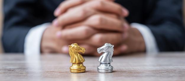 Złota i srebrna figura szachowego rycerza (konia) z biznesmenem. strategia, konflikt, zarządzanie, planowanie biznesowe, taktyka, polityka, komunikacja i koncepcja lidera