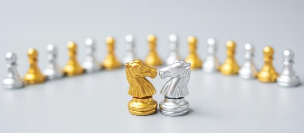 Złota i srebrna figura szachowego rycerza przed pionkiem