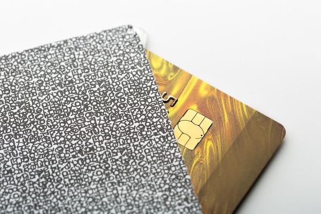 Złota karta kredytowa w kopercie na białym stole