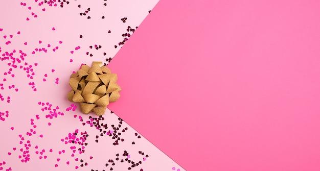 Złota kokarda i błyszczące wielokolorowe okrągłe konfetti rozrzucone na różowym tle