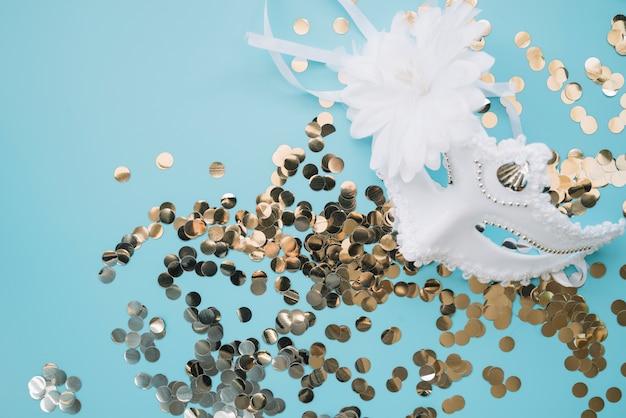 Złota konfetti i biała maska