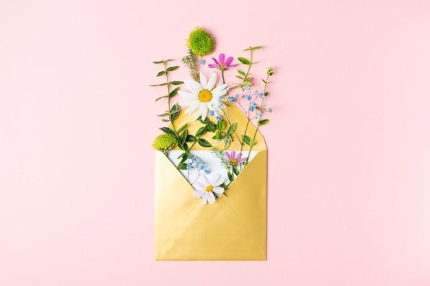 Złota koperta z pięknymi wiosennymi kwiatami ogrodowymi na różowym tle