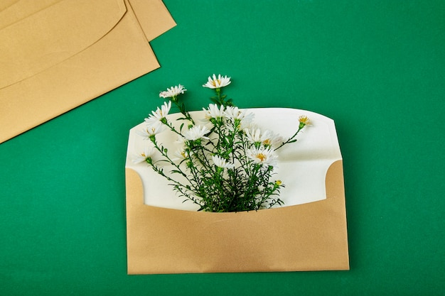 Złota koperta z wiosenną kompozycją kwiatową