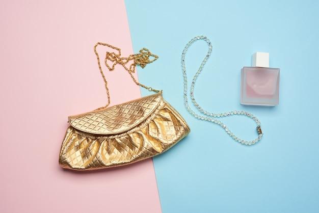 Złota kopertówka z różnymi kosmetykami i biżuterią na niebieskim tle