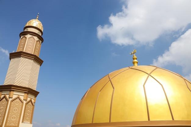 Złota kopuła i wysoka wieża meczetu na tle nieba