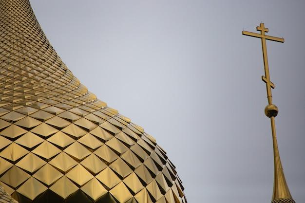 Złota kopuła kościoła na zbliżeniu po lewej stronie. a po prawej złoty krzyż. niebo jest między nimi. jest miejsce na kopię.