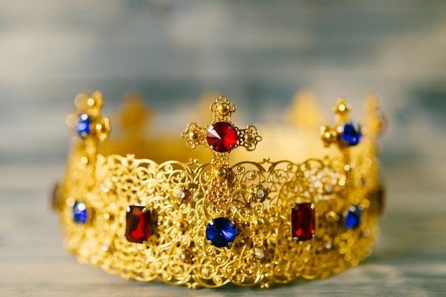 Złota korona wysadzana drogocennymi kamieniami do ślubu w kościele, na drewnianym tle