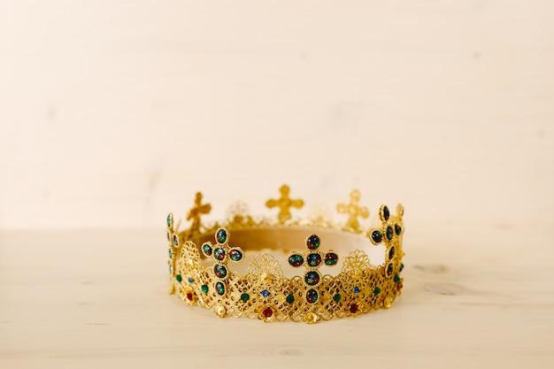 Złota korona wysadzana drogocennymi kamieniami i krzyżami na białym tle