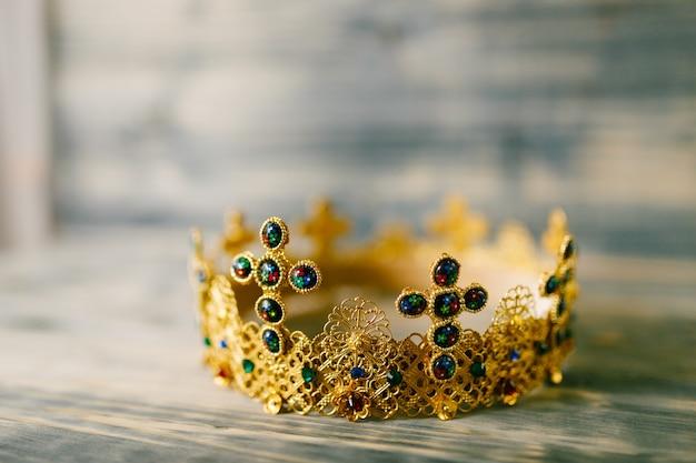 Złota korona wysadzana drogocennymi kamieniami na ślub w kościele na drewnianym stole
