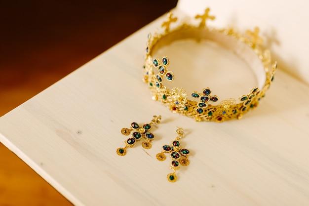 Złota korona z ślubnymi krzyżami i złote kolczyki wysadzane drogocennymi kamieniami