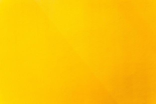 Złota lub żółta farba na fakturze ściany cementu jako tło