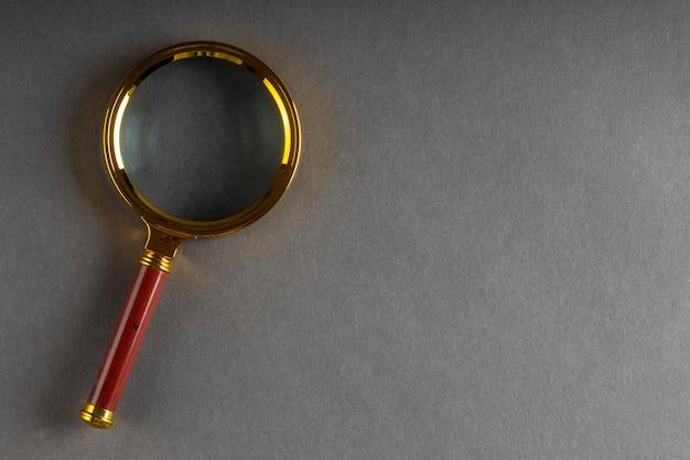 Złota lupa na czarnej powierzchni papieru