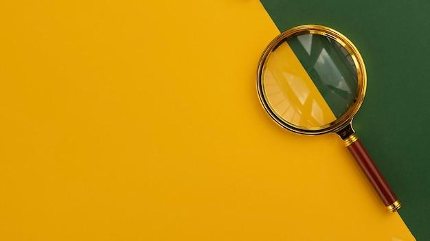 Złota lupa na jasnożółtym banerze w tle z copyspace