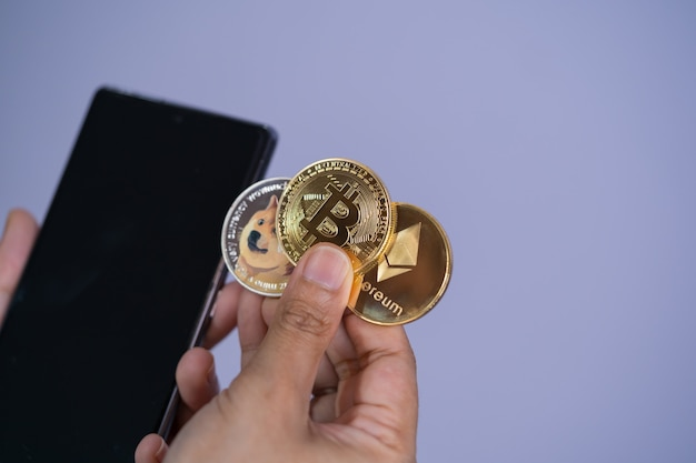 Złota moneta bitcoin dogecoin doge, grupa ethereum eth w zestawie z kryptowalutą na ręce kobieta lub dziewczyna i telefon komórkowy smartfon złożony umieść i podaj fioletowe tło. koncepcja zakupy online.