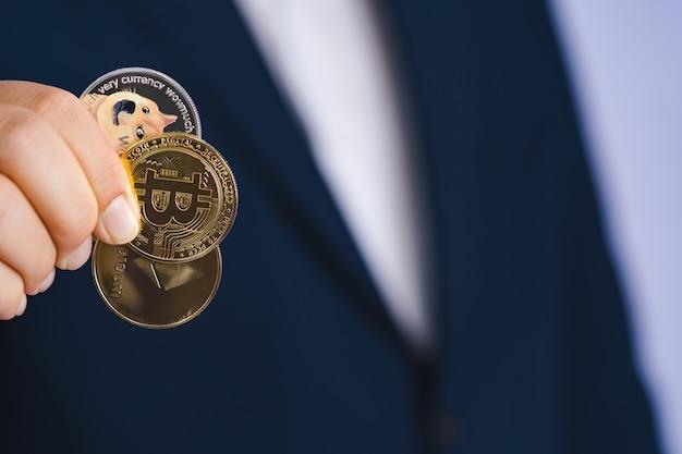 Złota moneta bitcoin dogecoin doge, grupa ethereum eth w zestawie z kryptowalutą na rękę człowiek biznesu ubrany w niebieski garnitur. zarchiwizuj i włóż i daj mi. zbliżenie i koncepcja fotografii makro.