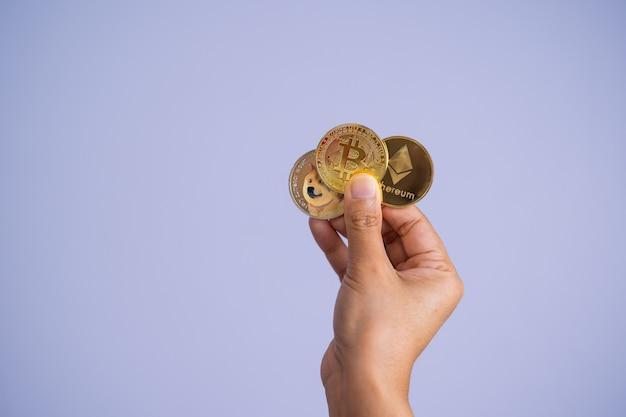 Złota moneta bitcoin dogecoin doge, grupa ethereum eth w zestawie z kryptowalutą na rękę kobieta lub dziewczyna złożona i włożona i daj mi fioletowe tło. zbliżenie i koncepcja fotografii makro.
