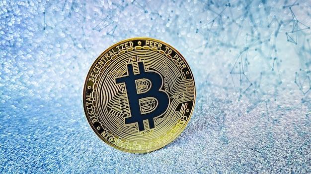 Złota moneta bitcoin i nieostre tło brokatu