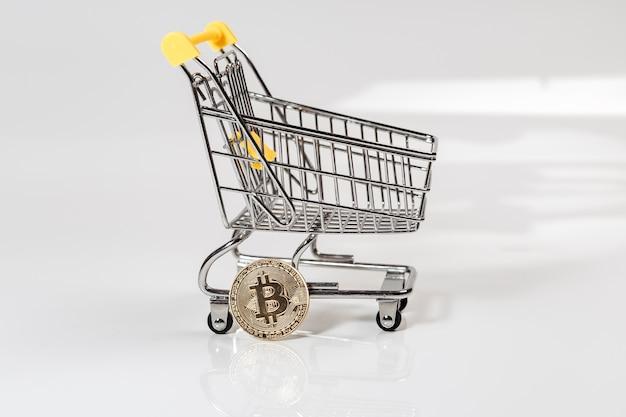 Złota moneta bitcoin lub btc ze znakiem kryptowaluty w pobliżu koszyka