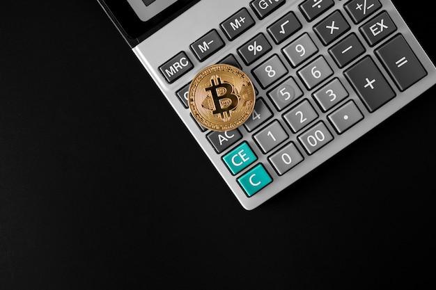 Złota moneta bitcoin na kalkulatorze