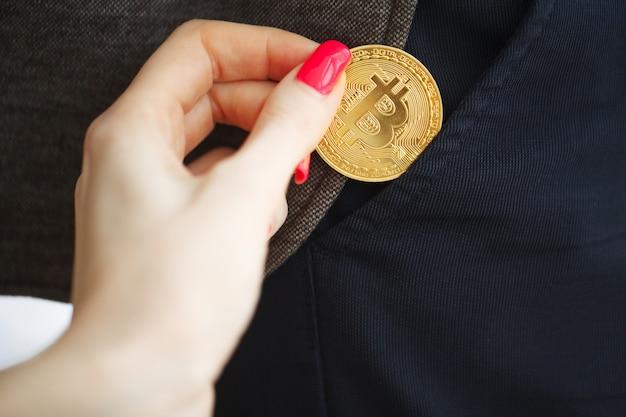 Złota moneta bitcoin w kieszeni. koncepcja kryptowaluty