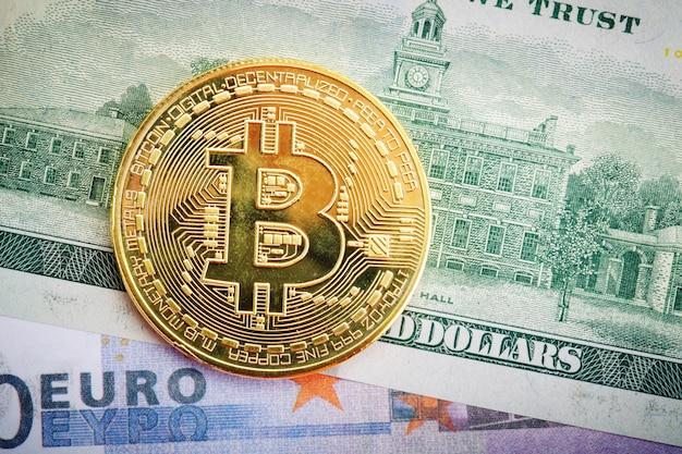 Złota moneta bitcoinów leży na dolarze i euro.