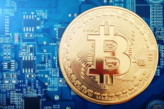 Złota moneta bitcoinów leży na karcie graficznej.