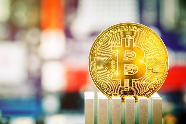 Złota moneta bitcoinów na tle płyty głównej.