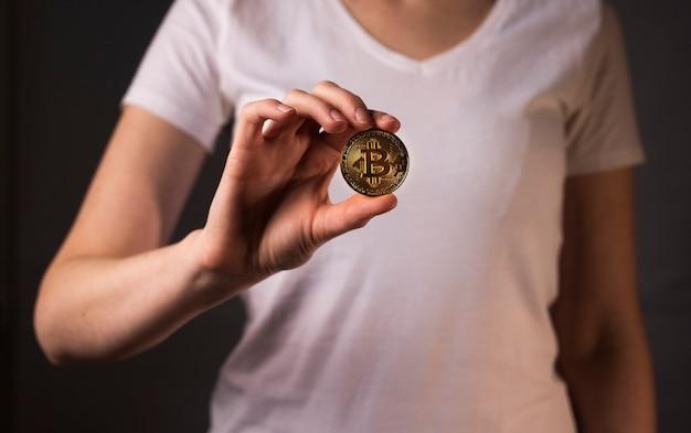 Złota moneta btc lub bitcoin trzymana w ręce bu przez kobietę.